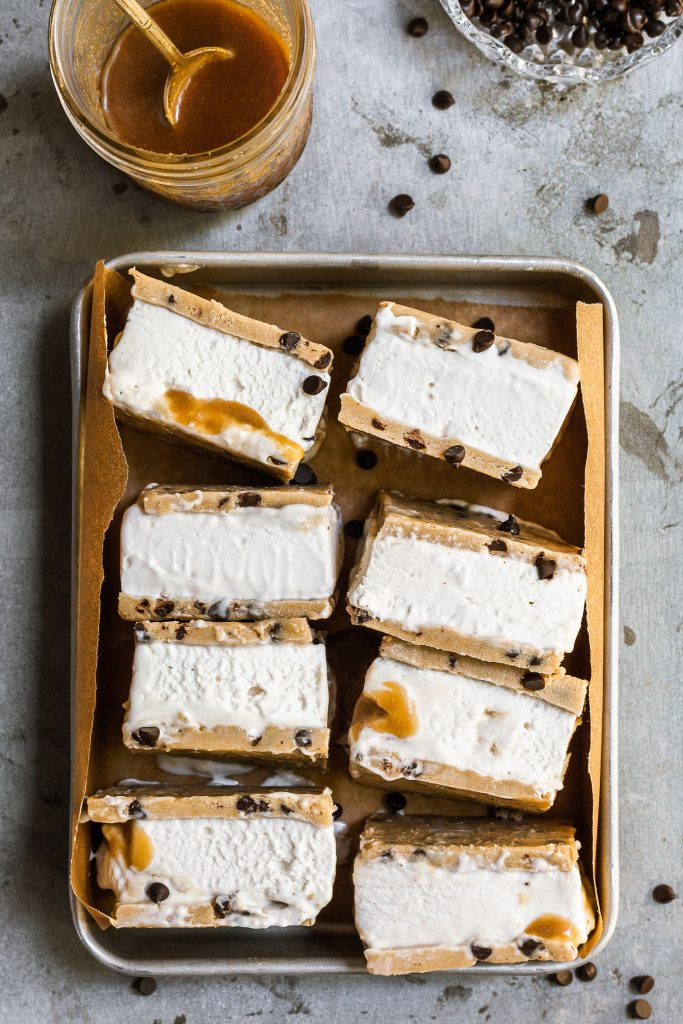 A rectangular aluminium tray filled with chocolate chip cookie dough ice cream sandwiches