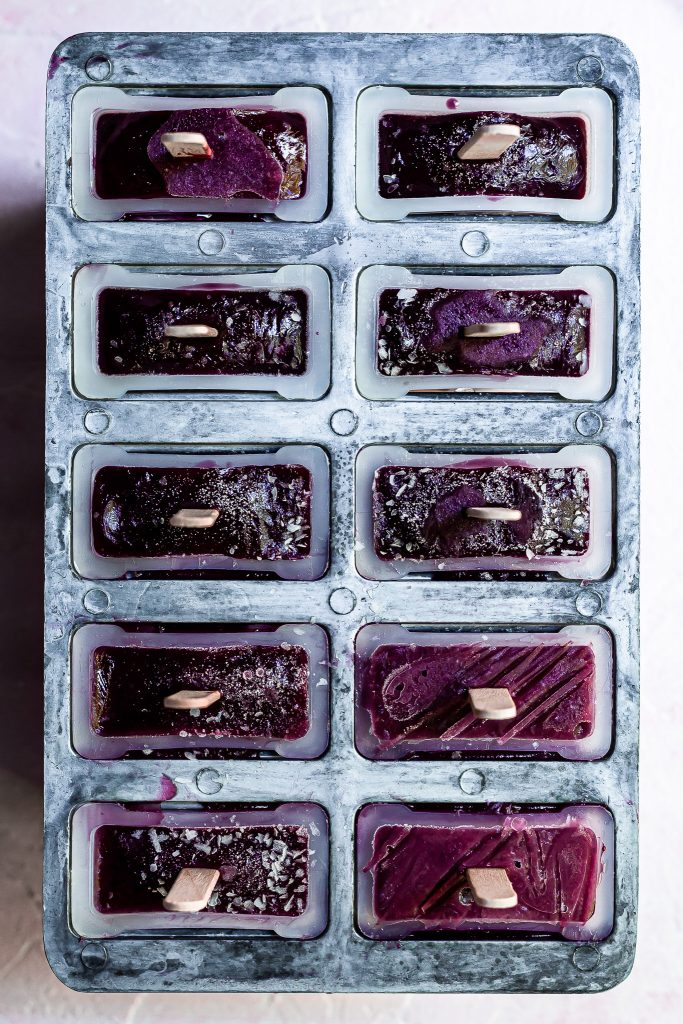 View looking down on popsicle mold straight out of the freezer containing purple popsicles with flecks of ice and frost on the surface