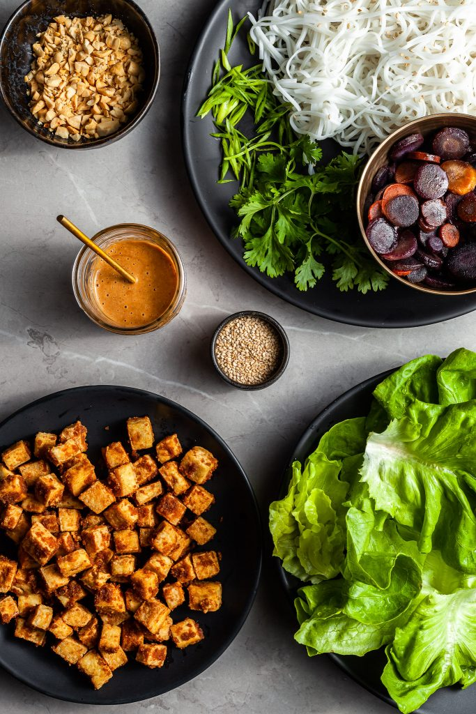the ingredients prepped in bowls for assembling the lettuce wraps - cooked rice noodles, herbs, glazed carrots, cubes of tofu, peanut sauce and lettuce leaves.
