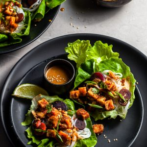 lettuce leaves on a black plate filled with tofu, rice noodles, carrots and drizzled with peanut sauce