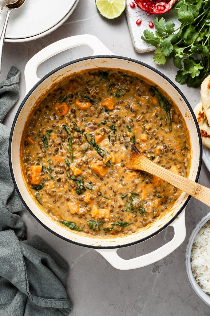 A white enamel cast iron pot filled with sweet potato lentil curry. Beside the pot are serving bowls, cooked rice and garnishes like lime wedges and cilantro