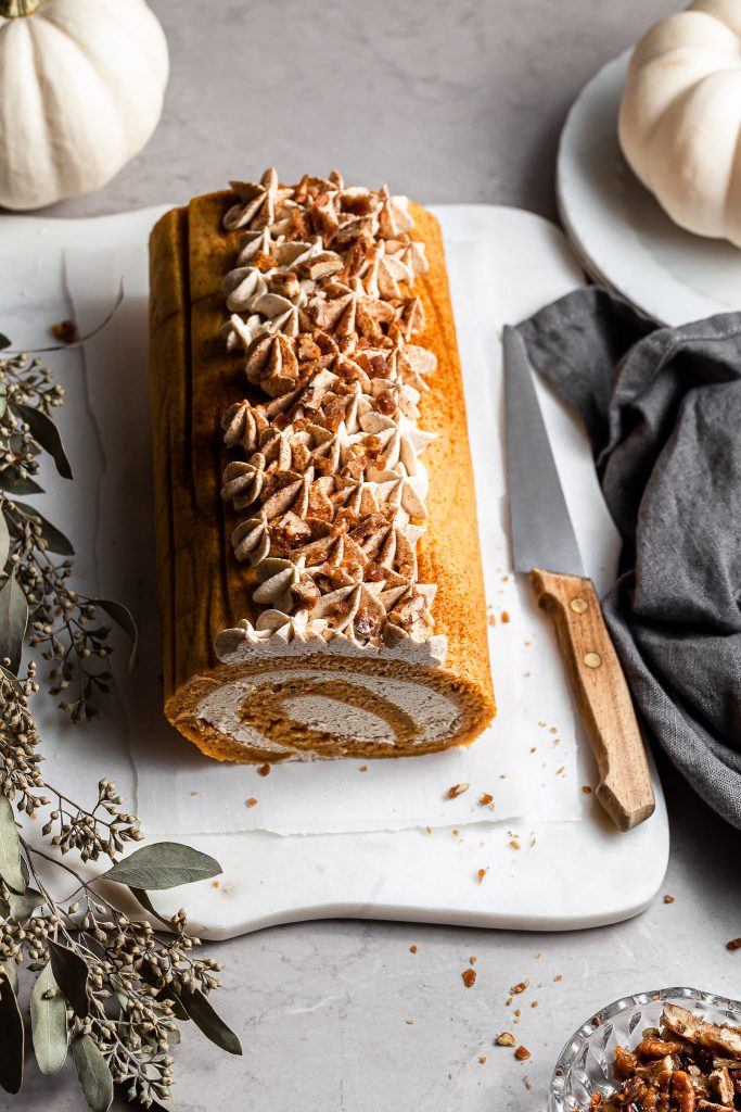 Unsliced pumpkin cake roll on a white marble platter