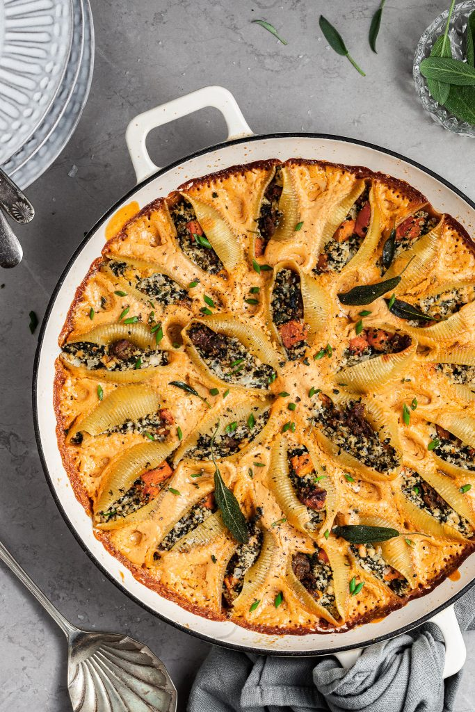 Baked pasta shells in a large white skillet garnished with fried sage