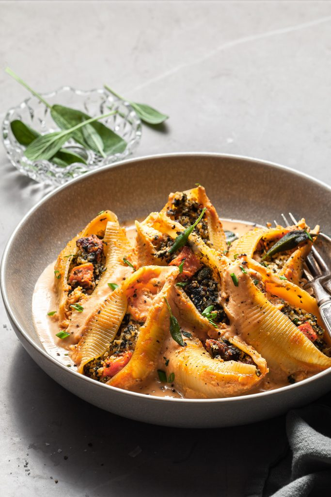 Stuffed pasta shells in a grey bowl with light pouring into the scene from behind a small bowl of fresh sage leaves