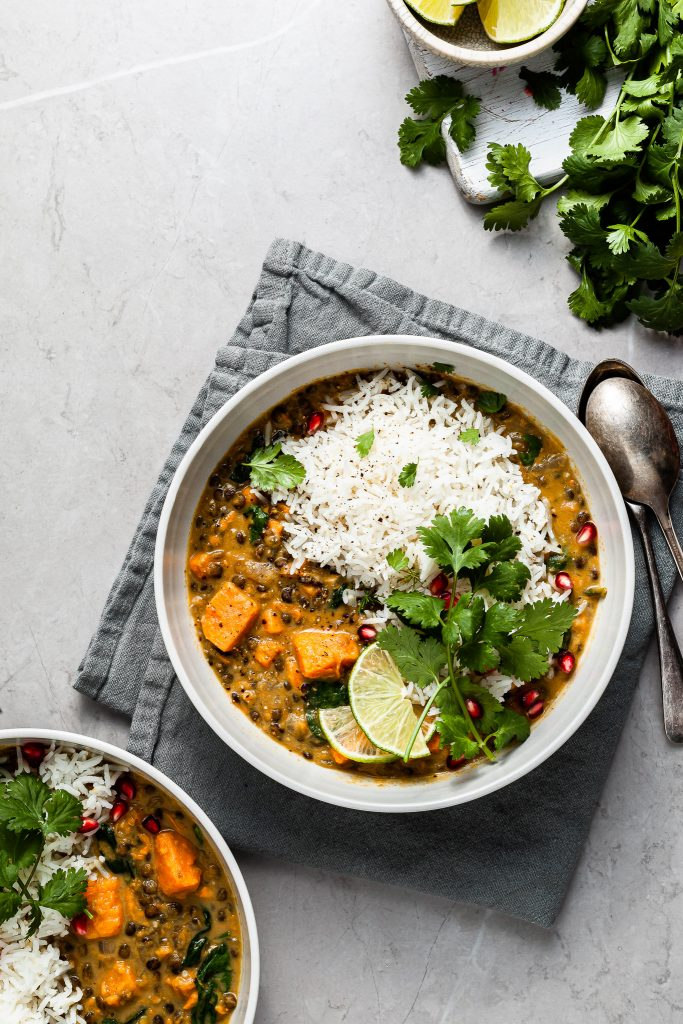 Two bowls of lentil sweet potato curry served with rice and cilantro