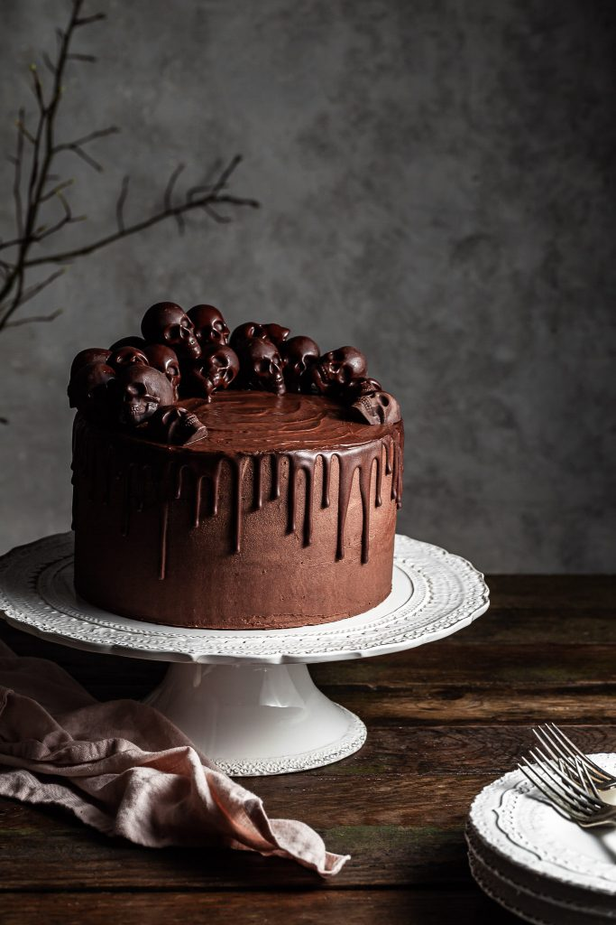 Chocolate layer cake on a white cake stand. A stack of white plates is in the foreground on top of which lies 3 silver forks.