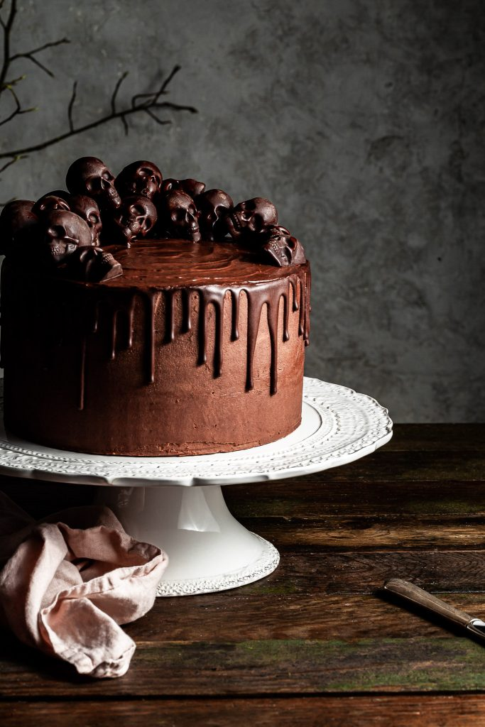 Cropped view of a chocolate layer cake covered in small chocolate skulls