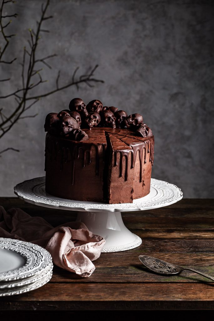 Chocolate layer cake with a chocolate ganache drip has two slices cut ready to be served with an antique spatula