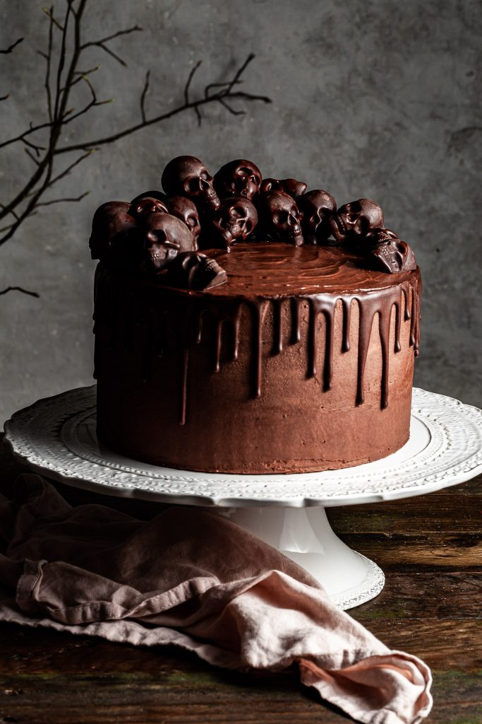 Chocolate layer cake with ganache drips and a half crown of small chocolate skulls on the top. The cake is on a white cake stand with a pink linen napkin beneath it.