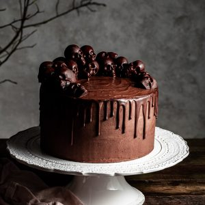 Chocolate layer drip cake decorated with small chocolate skulls, sitting on a white cake stand