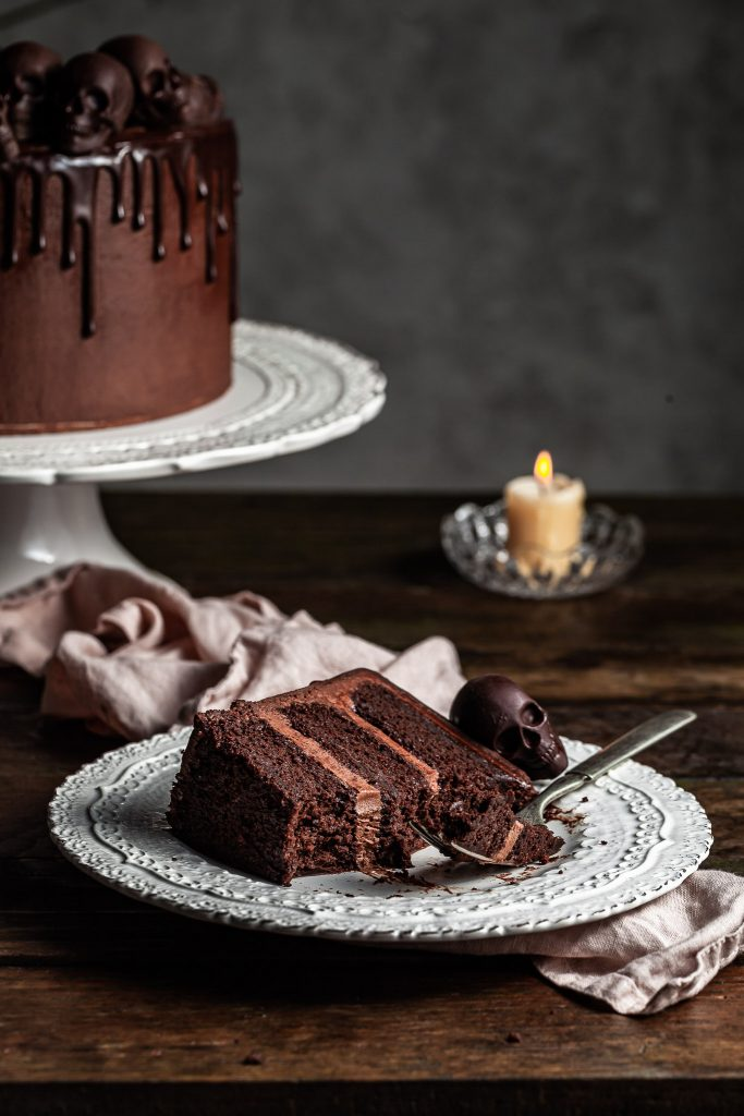 View of a slice of a triple layer chocolate cake with several bites missing and a fork resting on the plate it's lying on. A chocolate skull sits on the plate, while a candle glows in the background.