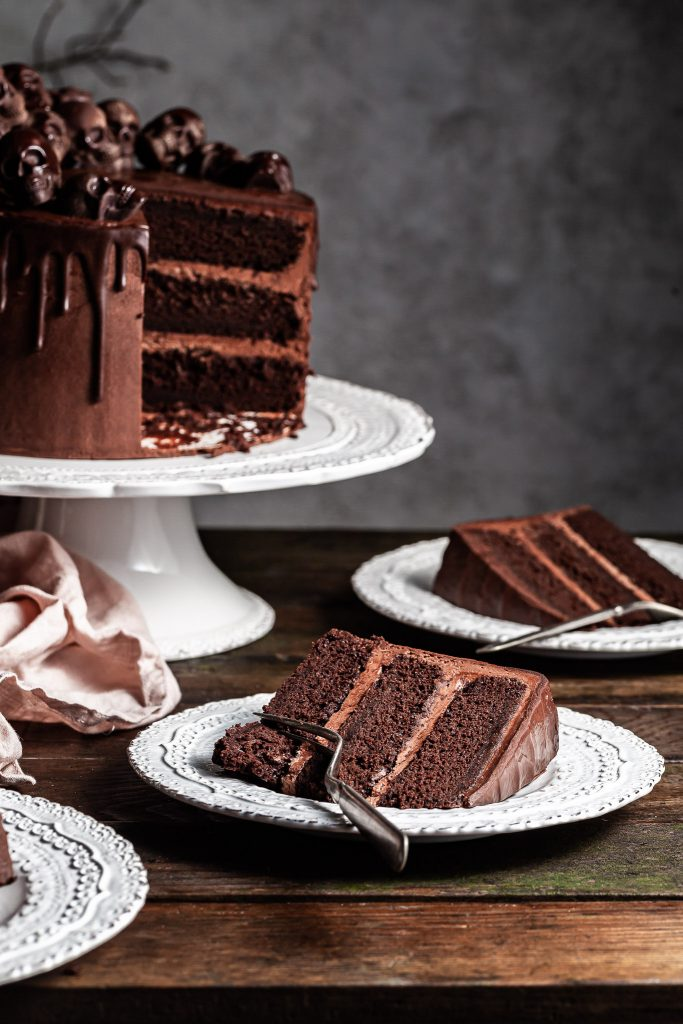 A slice of chocolate cake on a white plate, with another slice lies on a plate in the background beside a white pedestal cake stand holding the cut triple layer chocolate Halloween themed cake
