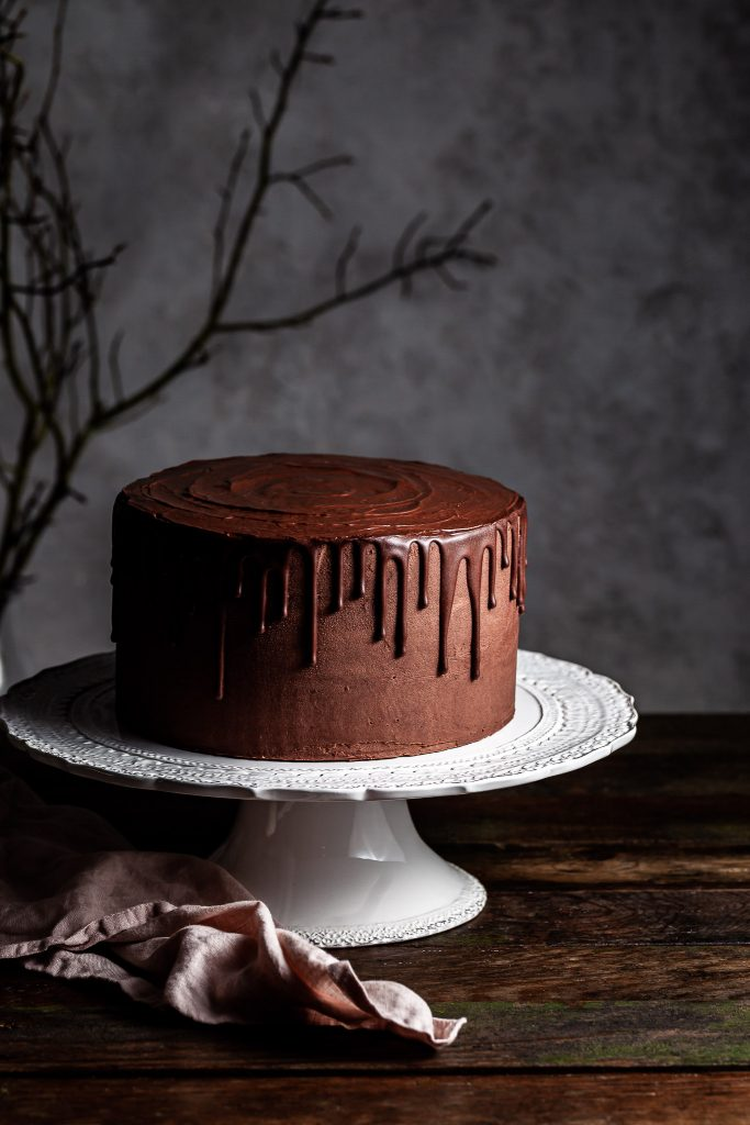 Vegan chocolate layer drip cake on a white cake stand with a branch in the dark background