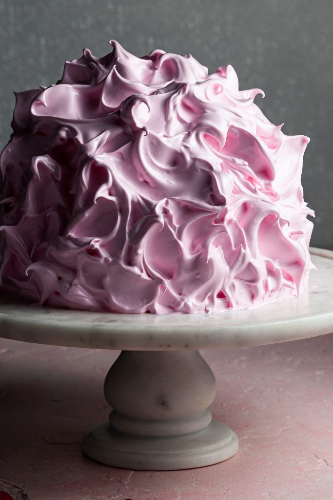 A pink baked Alaska before the meringue has been toasted, appearing glossy