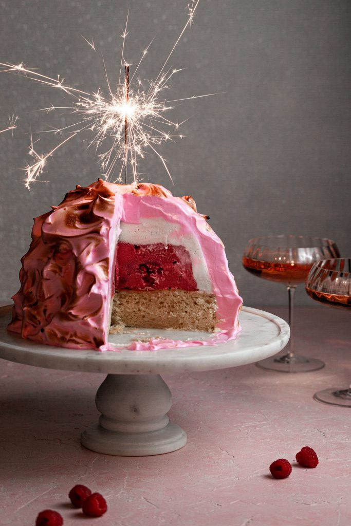 Pink baked Alaska with a lit sparkler on top beside 2 glasses of wine