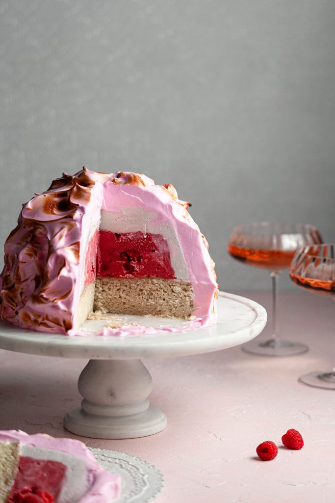A slice of baked alaska in the foreground, in front of a baked alaska covering in meringue sitting on a marble stand
