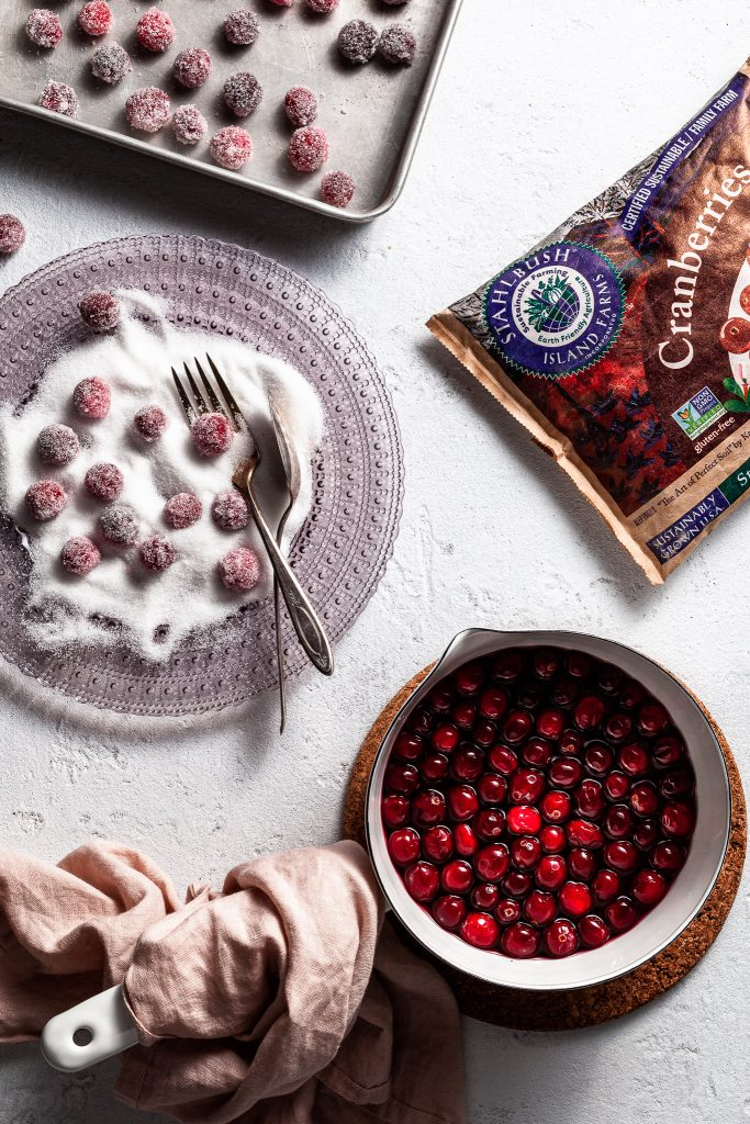 A view of sugared cranberries being made. A pot of cranberries in syrup at the bottom of the scene, with a glass plate filled with white sugar and a few cranberries already rolled in the sugar, a bag of frozen cranberries and a small baking sheet with sugared cranberries drying.