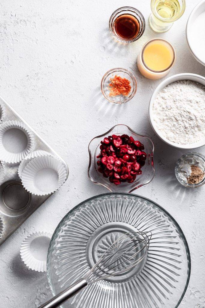 View looking down on a white counter where small bowls hold the ingredients for cranberry orange cupcake bases.