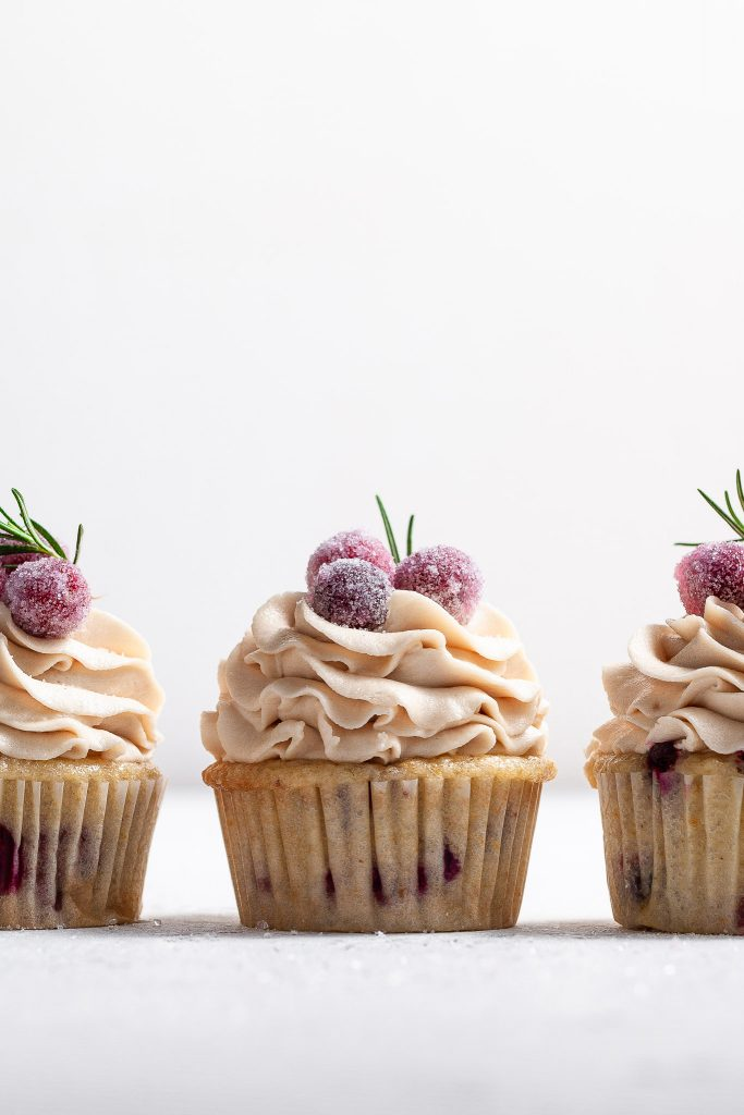 Eye level view of 3 frosted cupcakes, the bases appear to have red berries in the cake. The frosting is pipe high and topped with candied cranberries and a sprig of rosemary each.