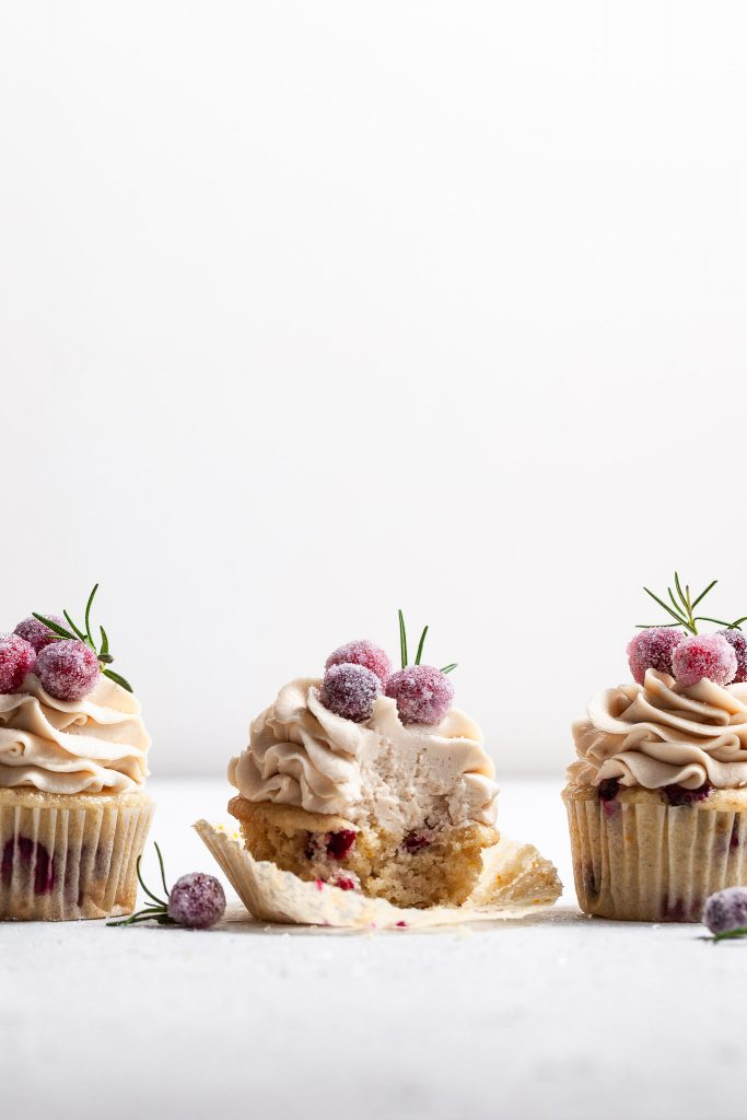 Three frosted cupcakes in a row at eye level, garnished with candied cranberries. The center cupcake has a bite missing.