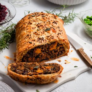 A vegan Wellington on a white marble platter sitting on a tabelscape with a bowl of whipped potatoes, green peas, cranberry sauce and wine glasses.