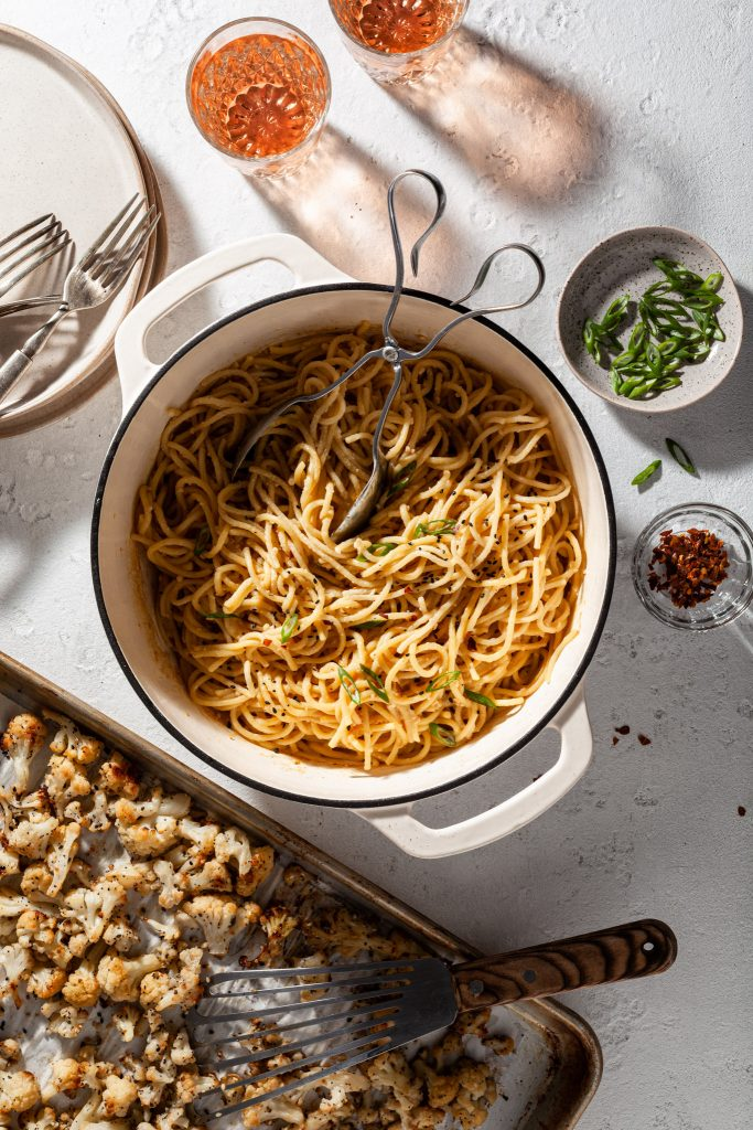 View of a white enamel Dutch oven pot filled with vegan garlic miso spaghetti noodles garnished with sesame seeds and slices of green onions. A baking sheet rests beside the Dutch oven, filled with roasted cauliflower.