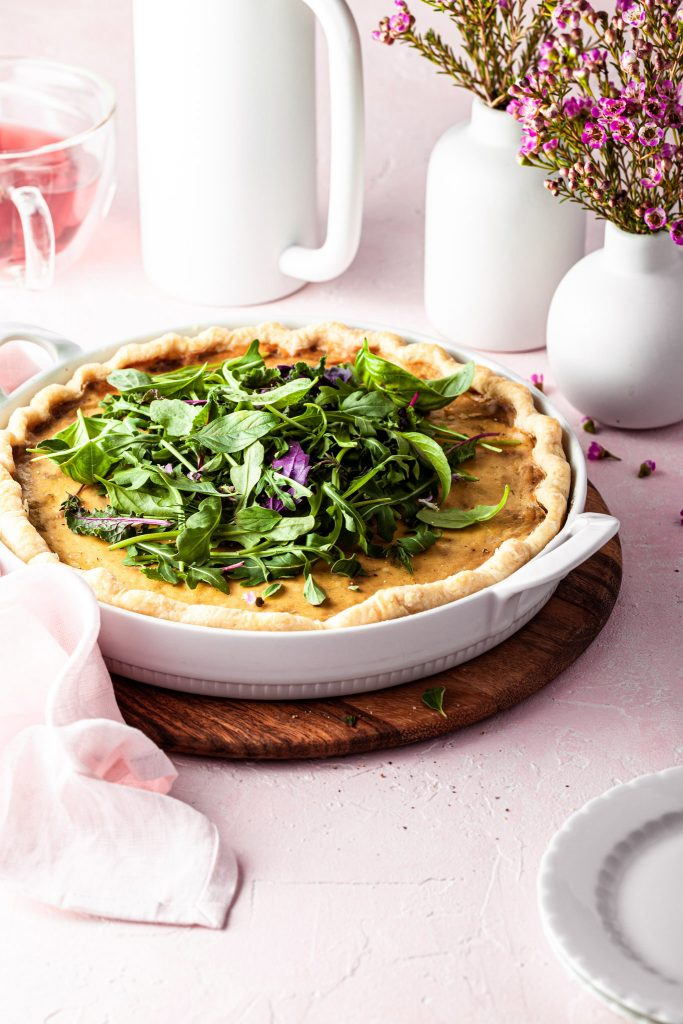 Side view of a vegan french onion quiche in a white porcelain baking dish. In the background there is a white French press and a mug of tea.