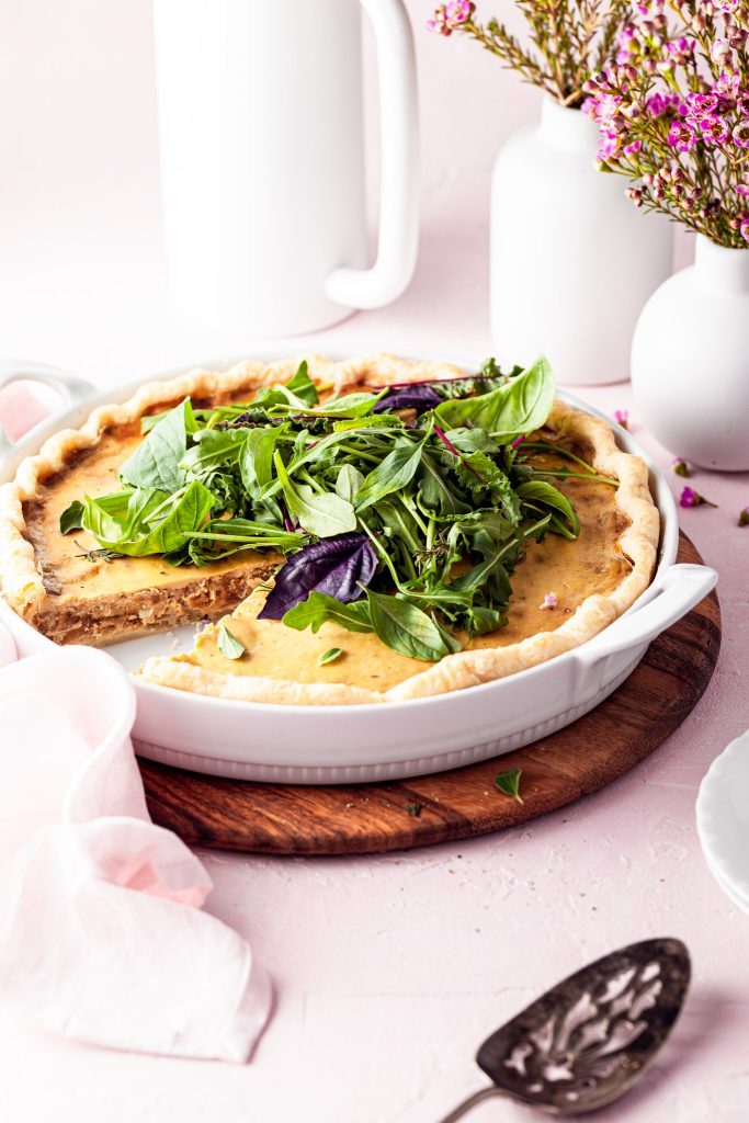 A quiche in a white tart dish with a slice served. White vases are in the background on this brunch table.