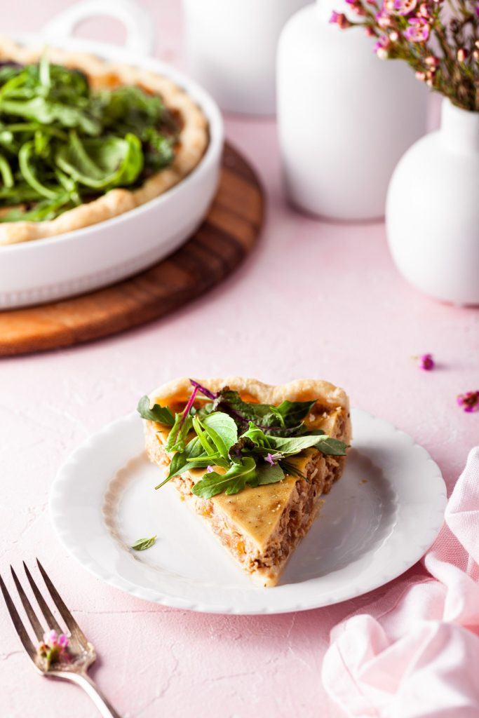 Slice of vegan French onion tart on a white plate topped with fresh herbs.