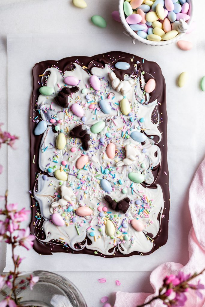 Chocolate bark made with dark chocolate layered with white chocolate and topped with pastel candy coated almonds on a white marble slab