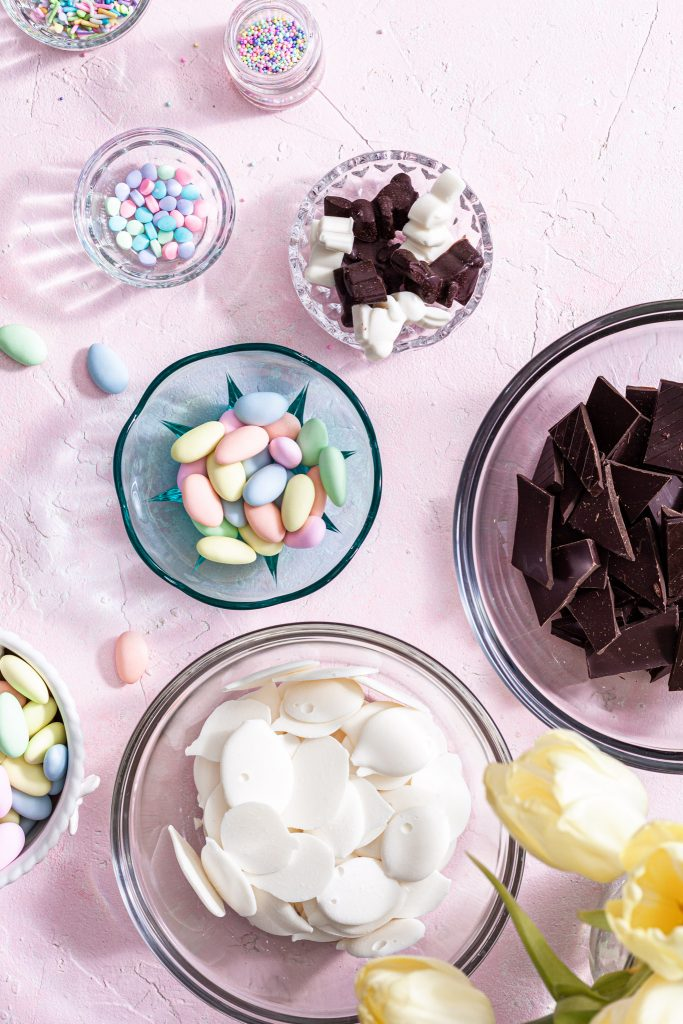 The ingredients for chocolate bark are laid out in bowls on a pink counter.