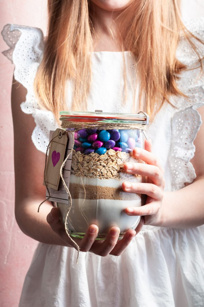 A little girl with long blond hair handing a gift of cookie mix in a glass jar.