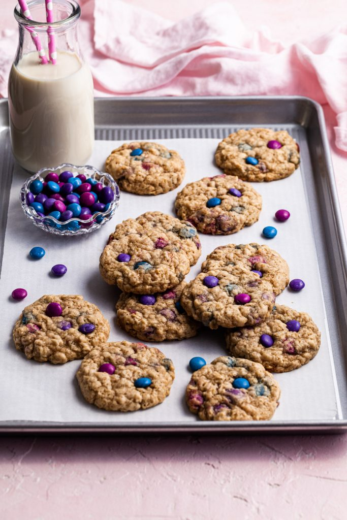 Cookies on a baking sheet with a bottle of milk and a small glass bowl of candies.