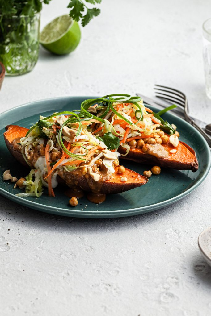 Side view of a green plated filled with two halves of a baked sweet potato stuffed with crispy chickpeas, Thai curry peanut sauce and a simple cabbage slaw.
