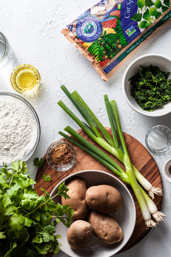 An image showing the ingredients for the stuffed flatbread including potatoes, spinach, oil, flour, salt, water, cilantro, spices and green onions.