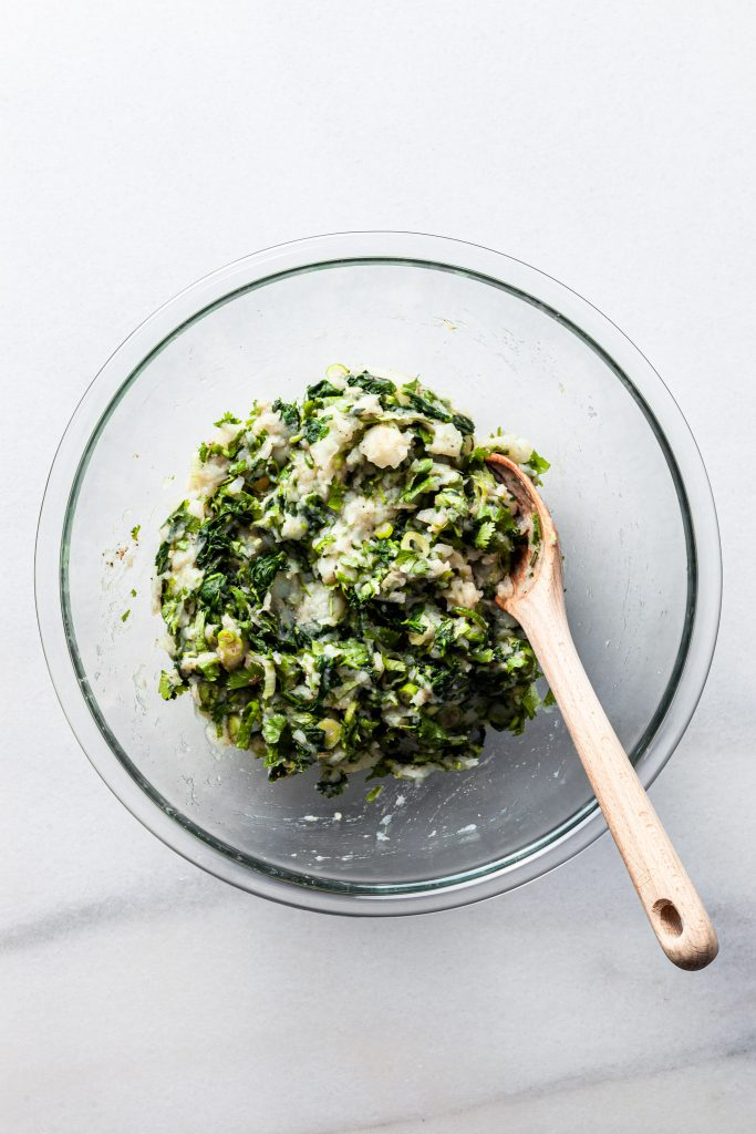 A glass bowl filled with a mixture of mashed potatoes, chopped spinach, sliced green onions, cilantro and spices.