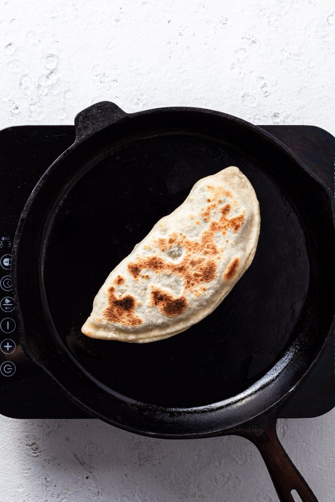 Bolani or stuffed flatbread cooked in a cast iron skillet.