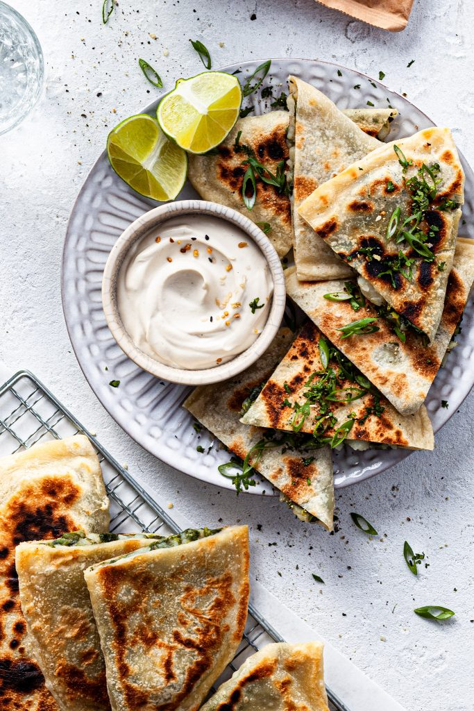 A view looking down on a white plate filled with pieces of stuffed flatbread served with whipped yogurt, sitting beside a wire cooling rack with fresh cooked bolani.