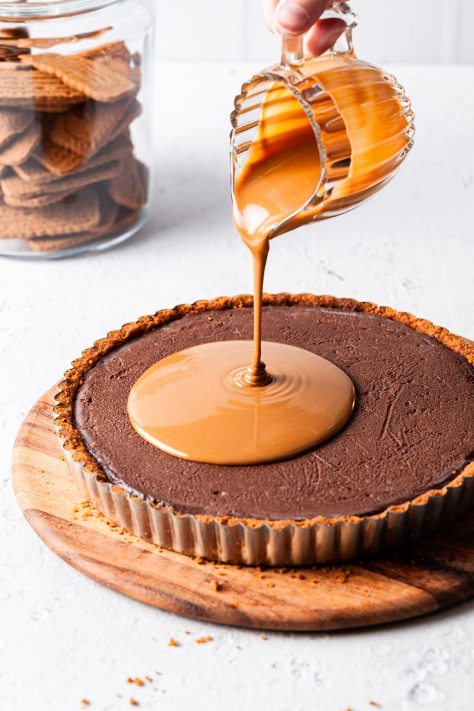 A small glass jug filled with melted Biscoff spread is pouring over the chocolate cookie tart as the final layer.