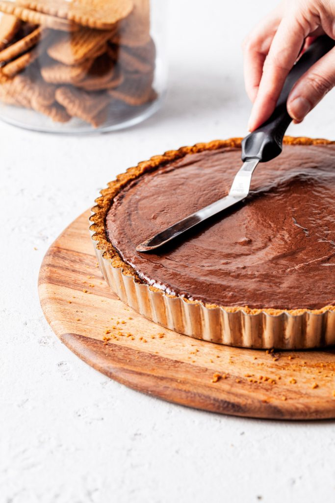 An image of a hand holding an offset spatula smoothing the chocolate Biscoff filling over the cookie crumb crust before chilling.