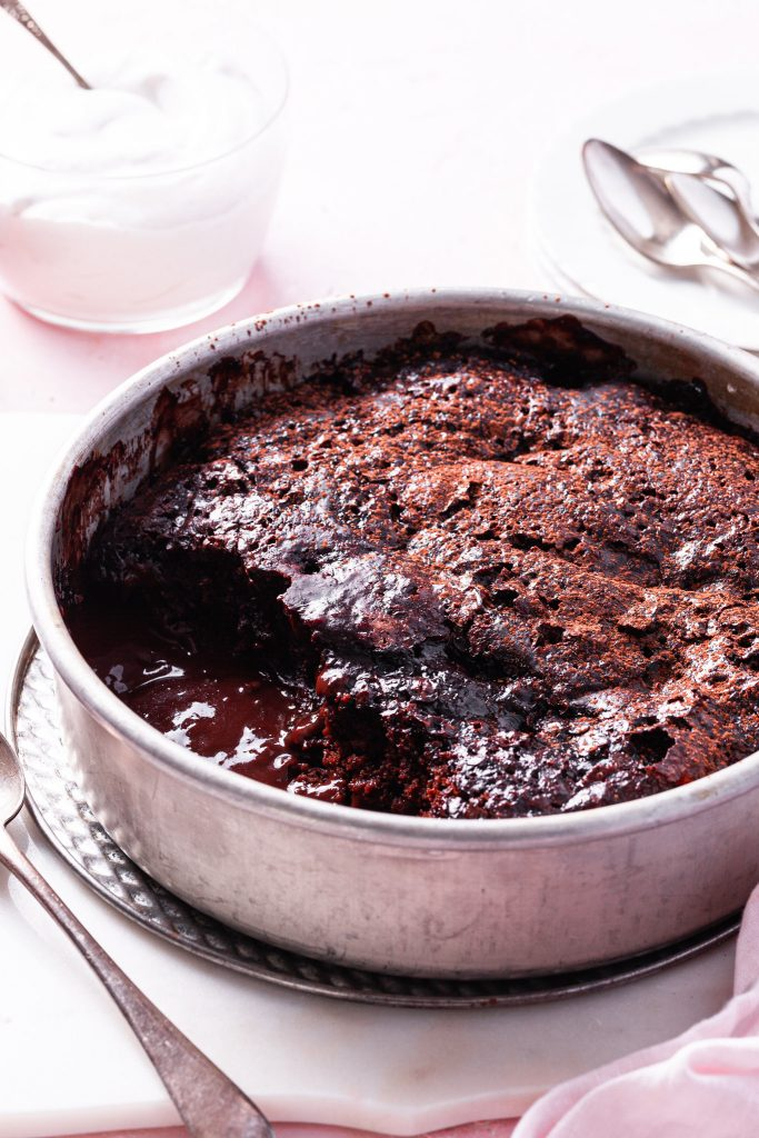 A side view of the self-saucing chocolate strawberry pudding cake with a scoop missing exposing the glossy chocolate sauce on the bottom.
