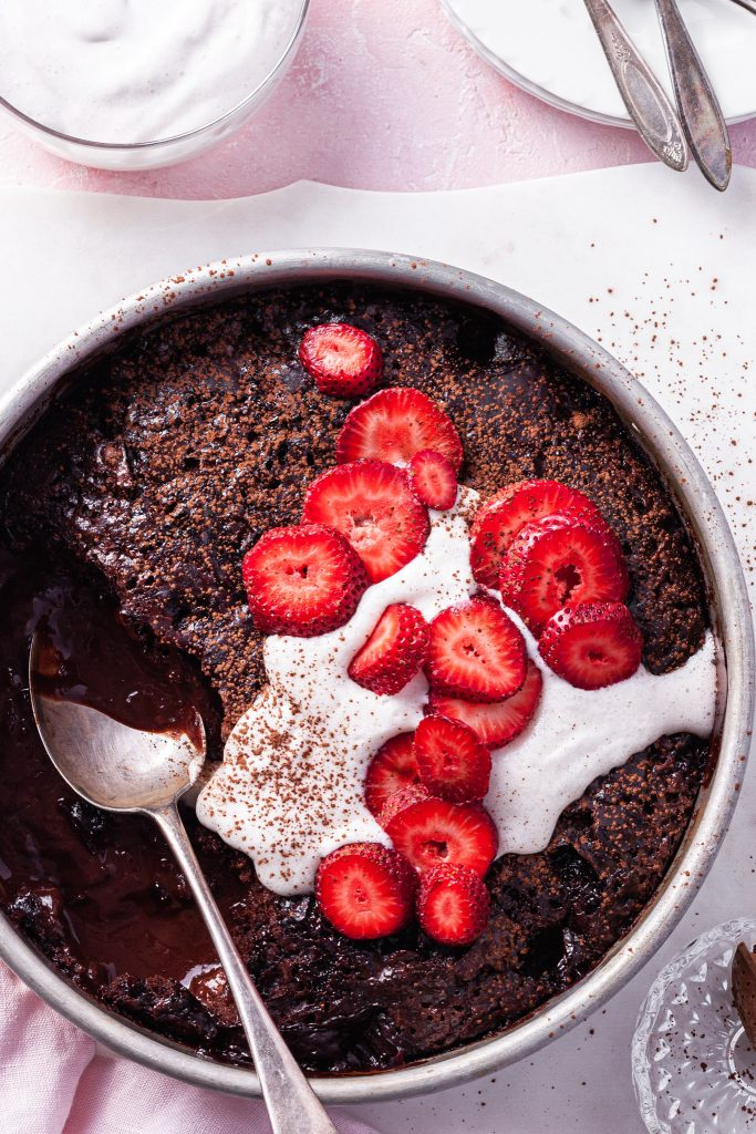 View looking down on a baking dish filled with chocolate cake baked on top of sauce. One scoop has been removed, and the top is garnished with vegan cream and sliced strawberries.