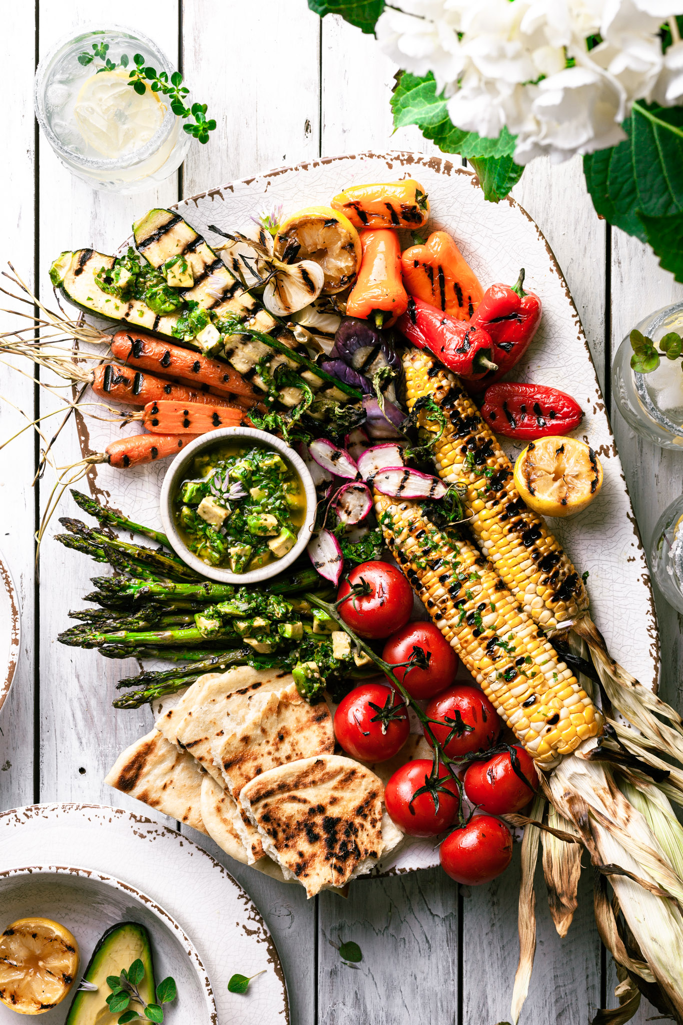 A white platter filled with grilled vegetables covered in avocado chimichurri sauce.