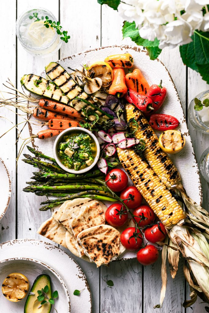 A white platter filled with grilled vegetables and a small bowl of chimichurri sauce on a white picnic table.