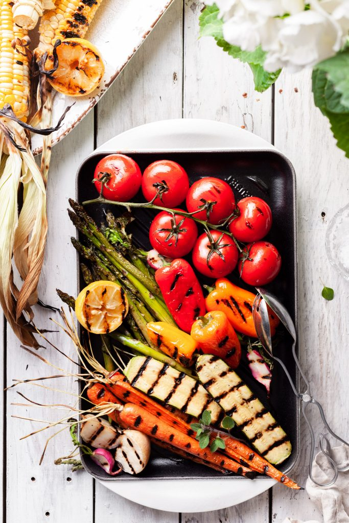 A white enameled cast iron grill covered in grilled vegetables.