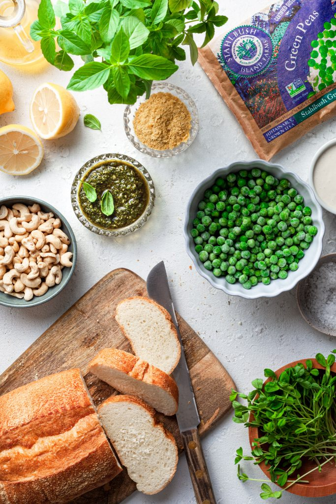 A white counter covered in the ingredients needed for this pesto pea and vegan ricotta toast.