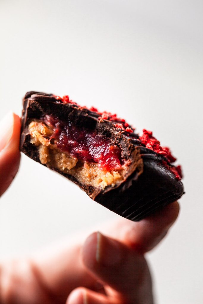 A hand holding a peanut butter and jelly chocolate cup with a bite missing.